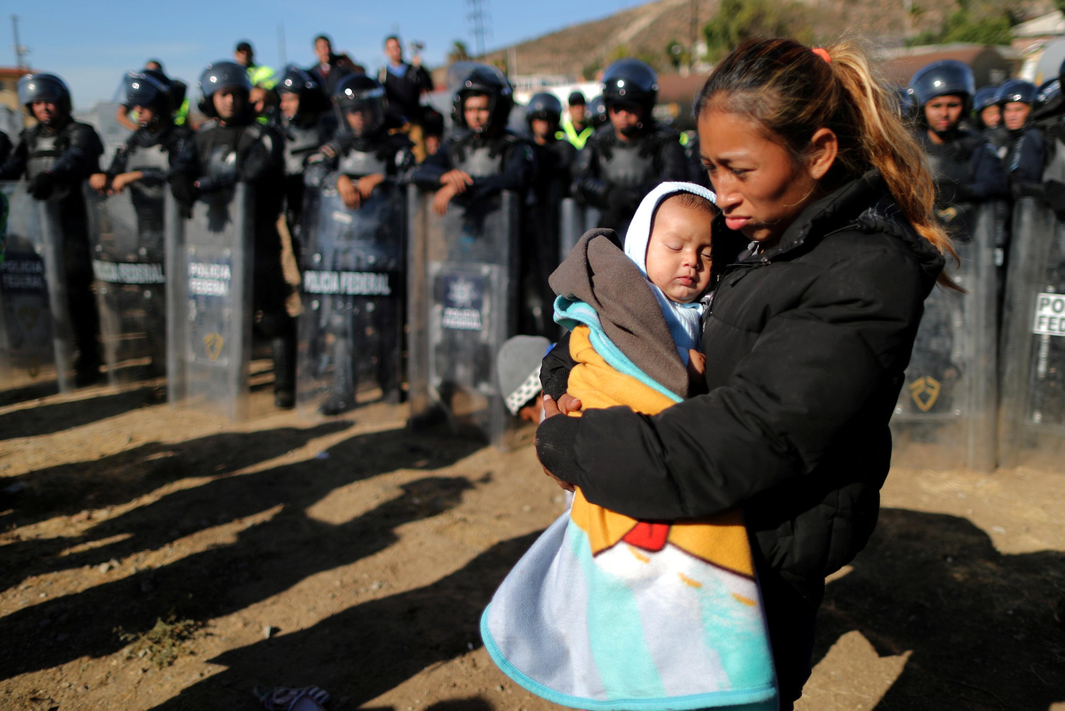 إحدى المهاجرين تحمل طفلها