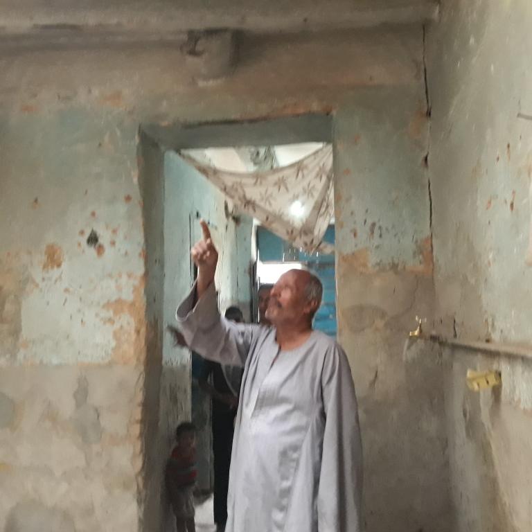 7 مسن يشير إلى سقف منزله