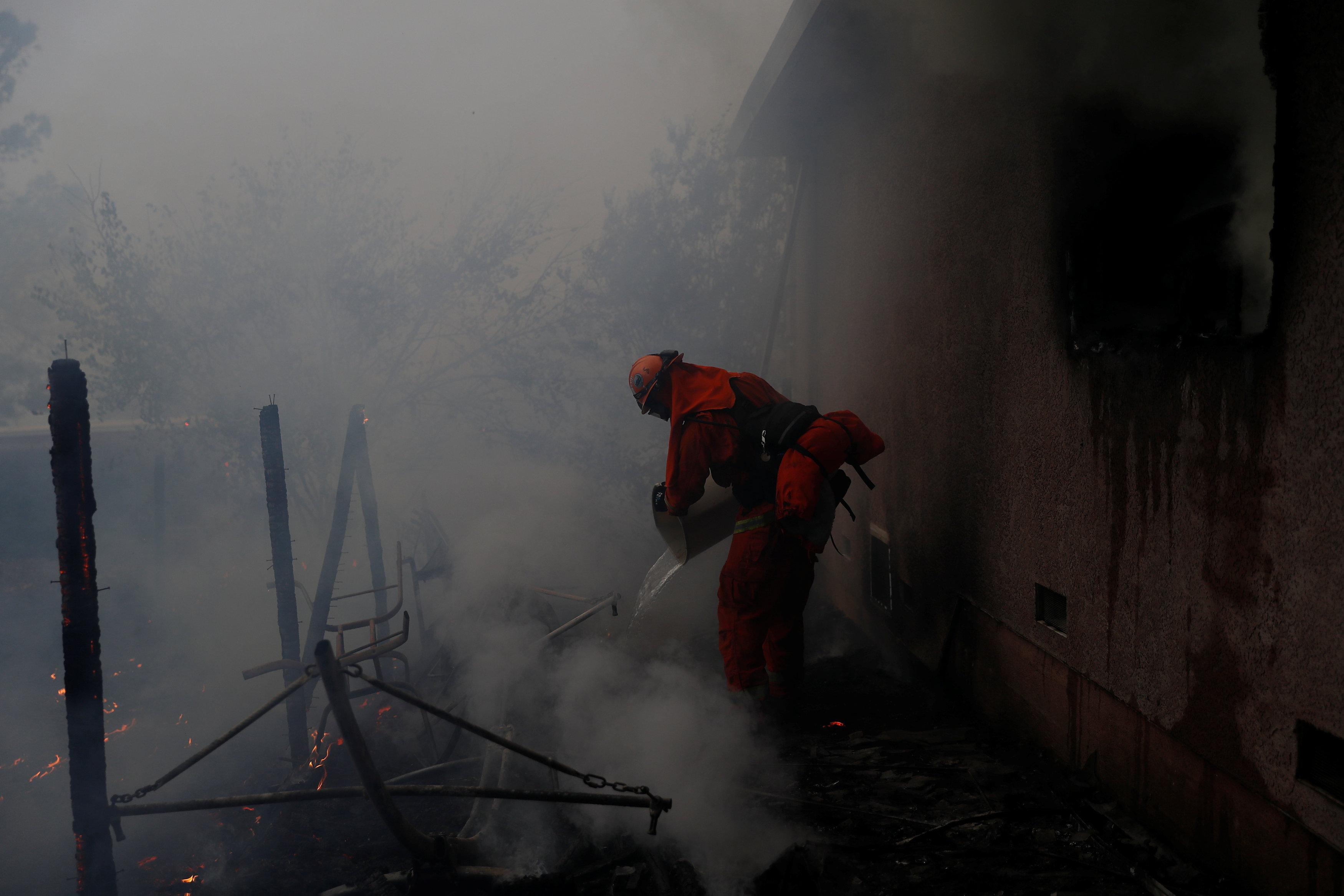 أحد رجال الإنقاذ يطفئ النيران