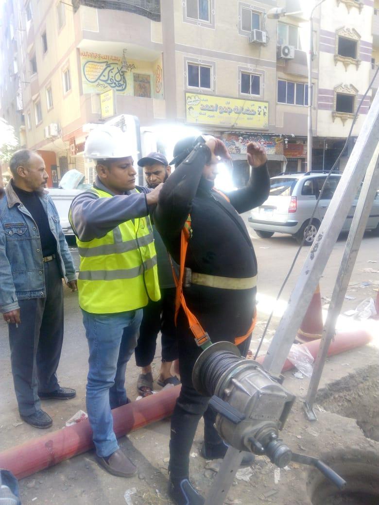 عمال شركة مياه الجيزة يطهرون بلاعات الصرف بامبابة (1)