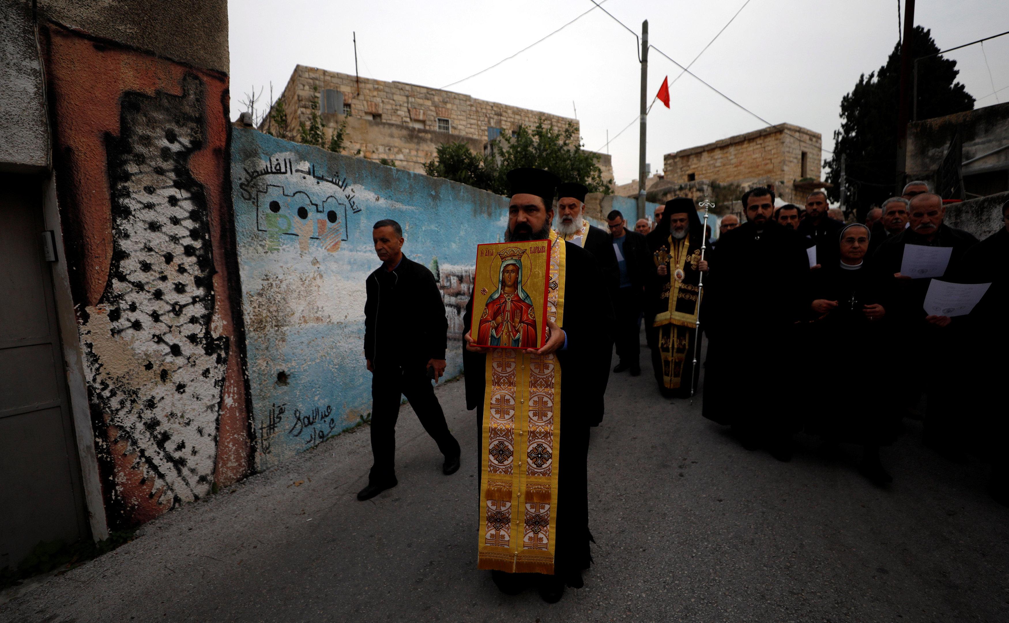 رجال الدين يزفون صورة القديسة بربارة فى شوارع القرية