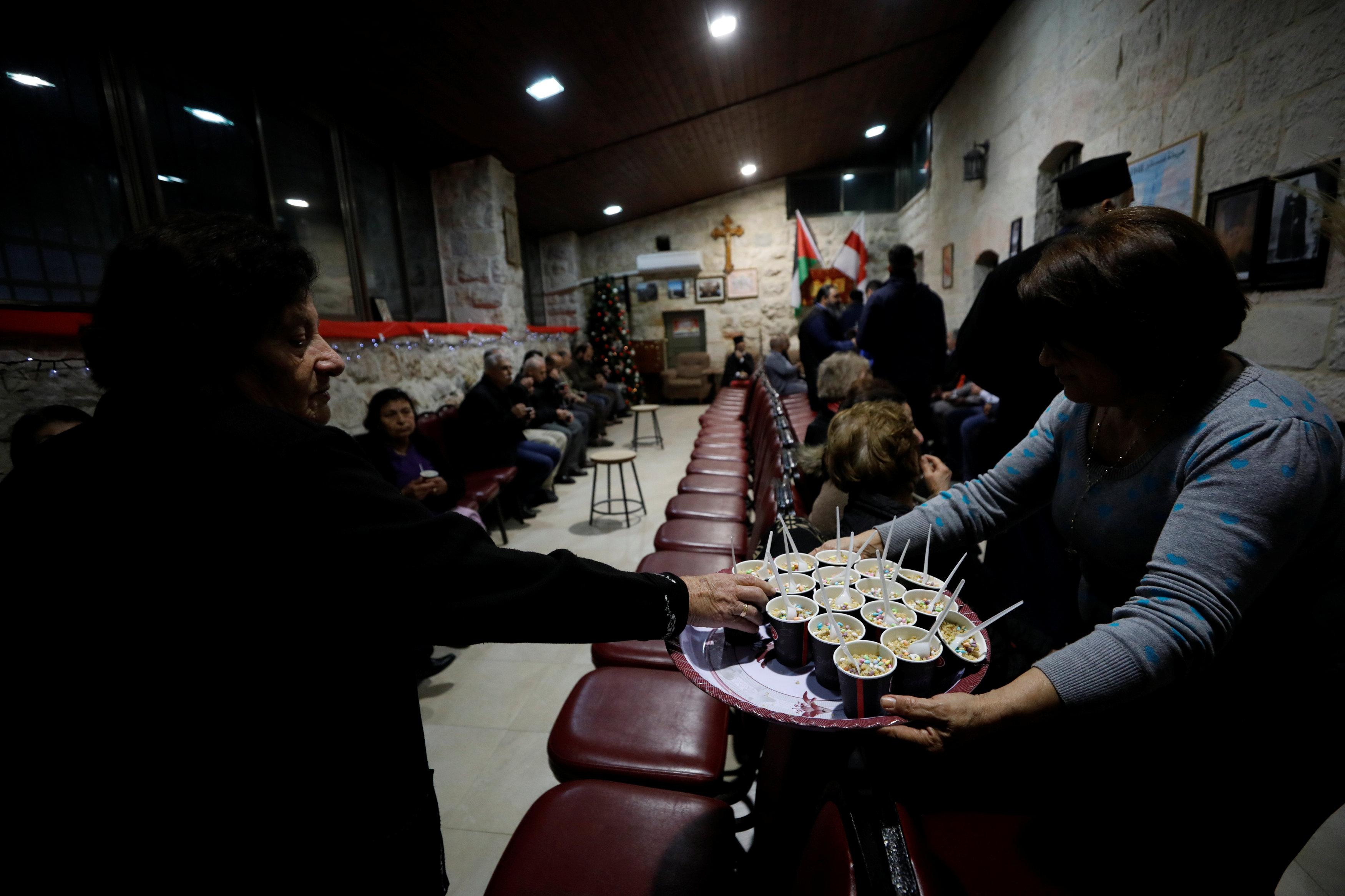 فلسطينيون يوزعون مأكولات تقليدية خاصة بالمناسبة