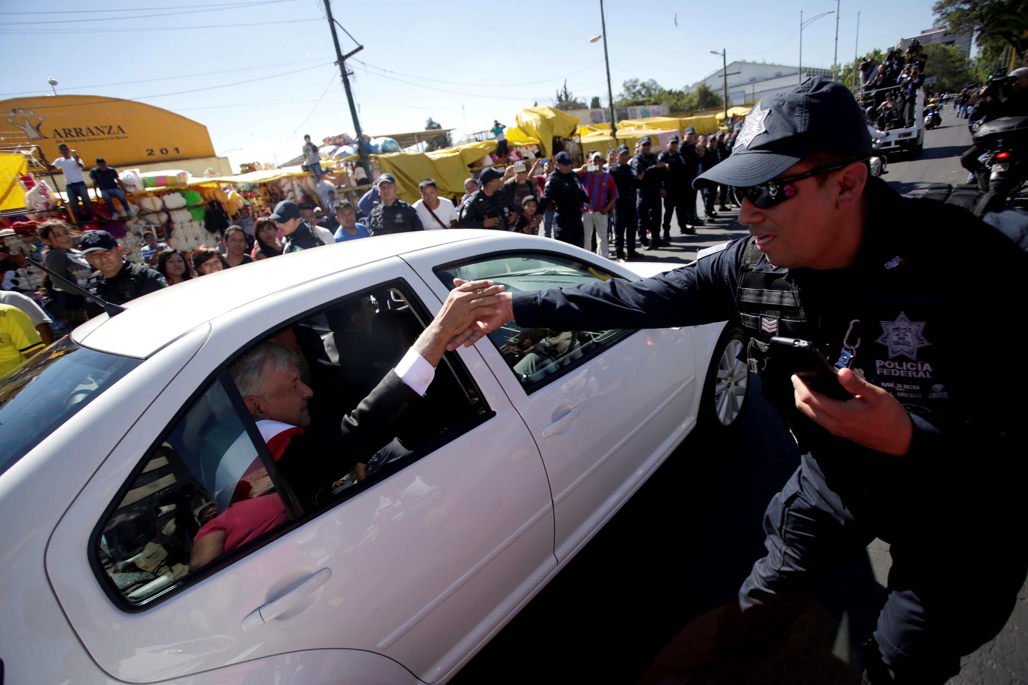 ضابط شرطة فيدرالي يصافح الرئيس الجديد للمكسيك