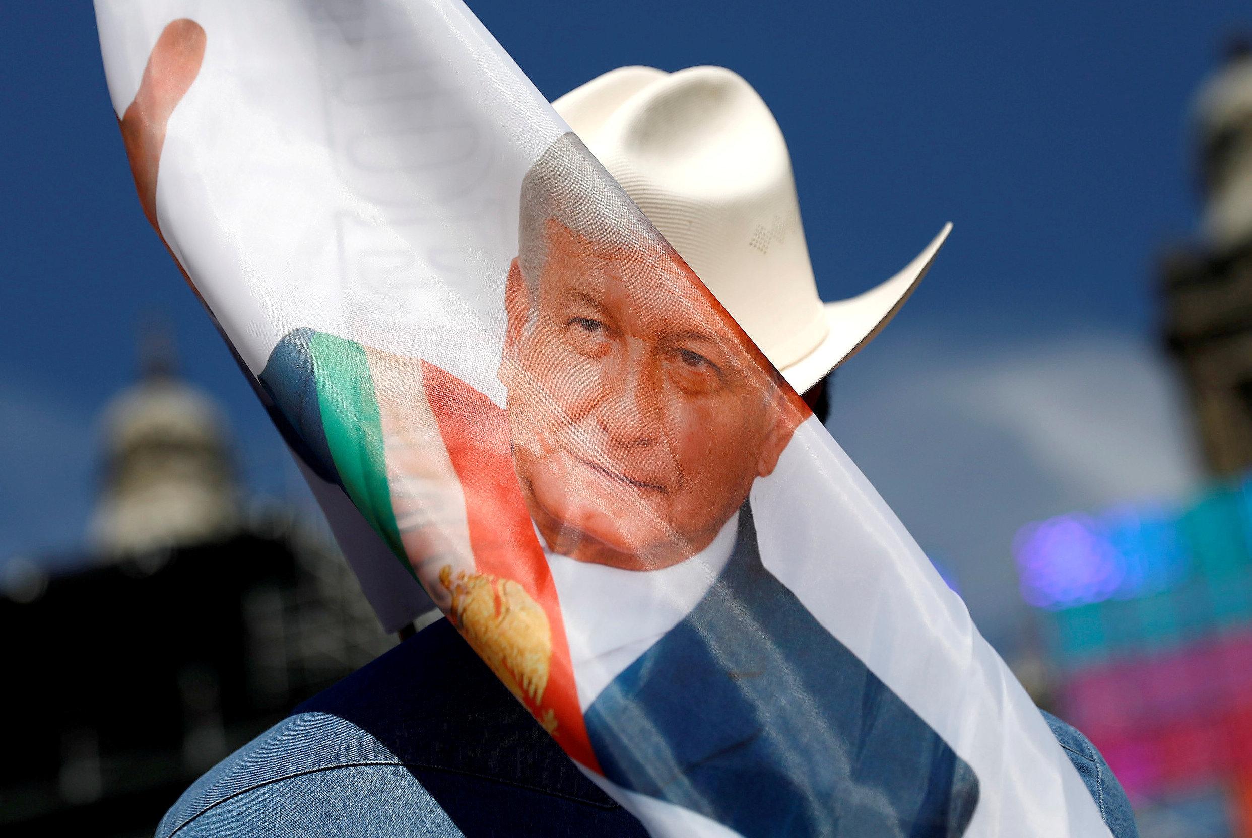 مؤيد لرئيس المكسيك الجديد يحمل لافتة أثناء انتظار وصوله