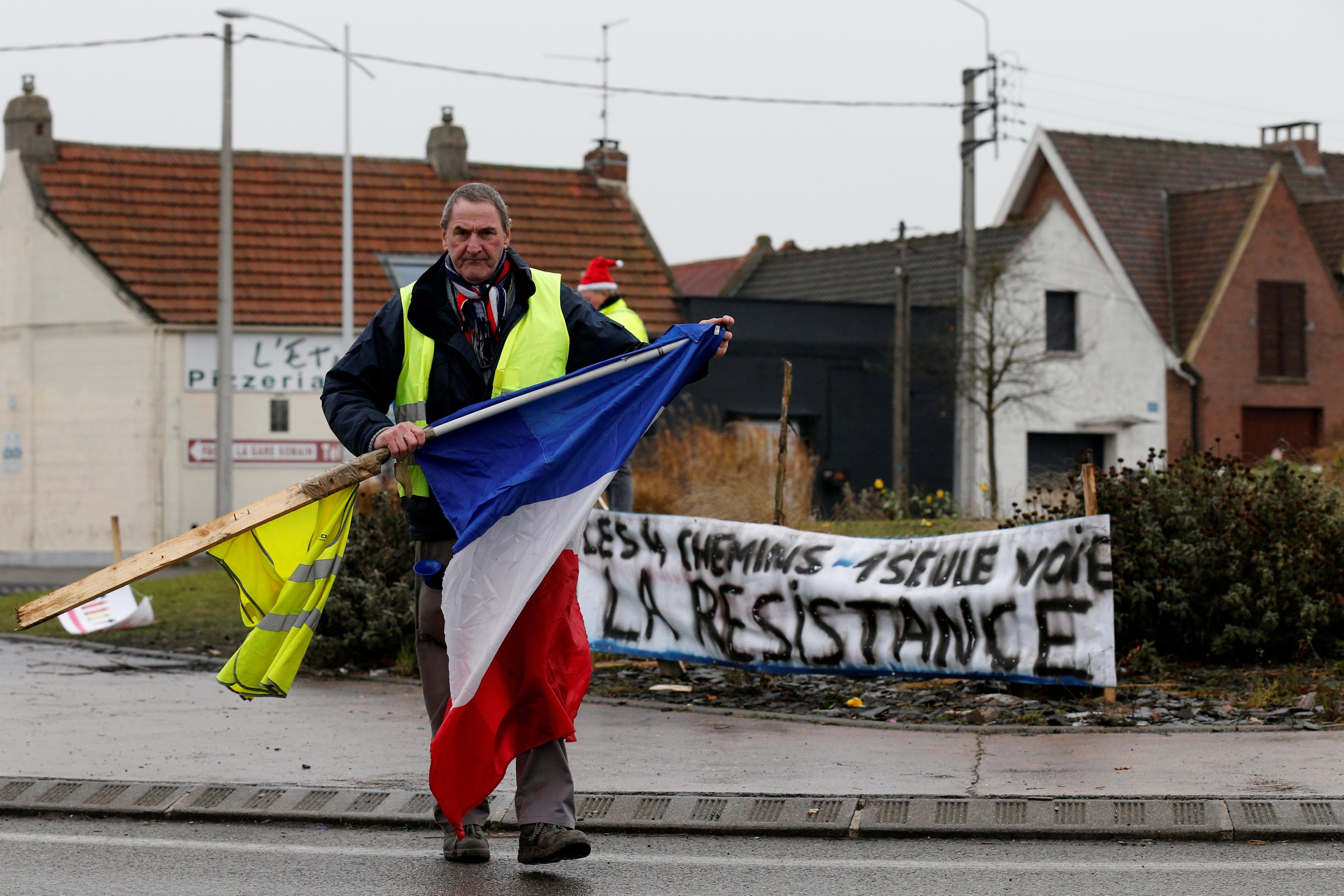 متظاهر يتظاهر مرتديا سترة صفراء
