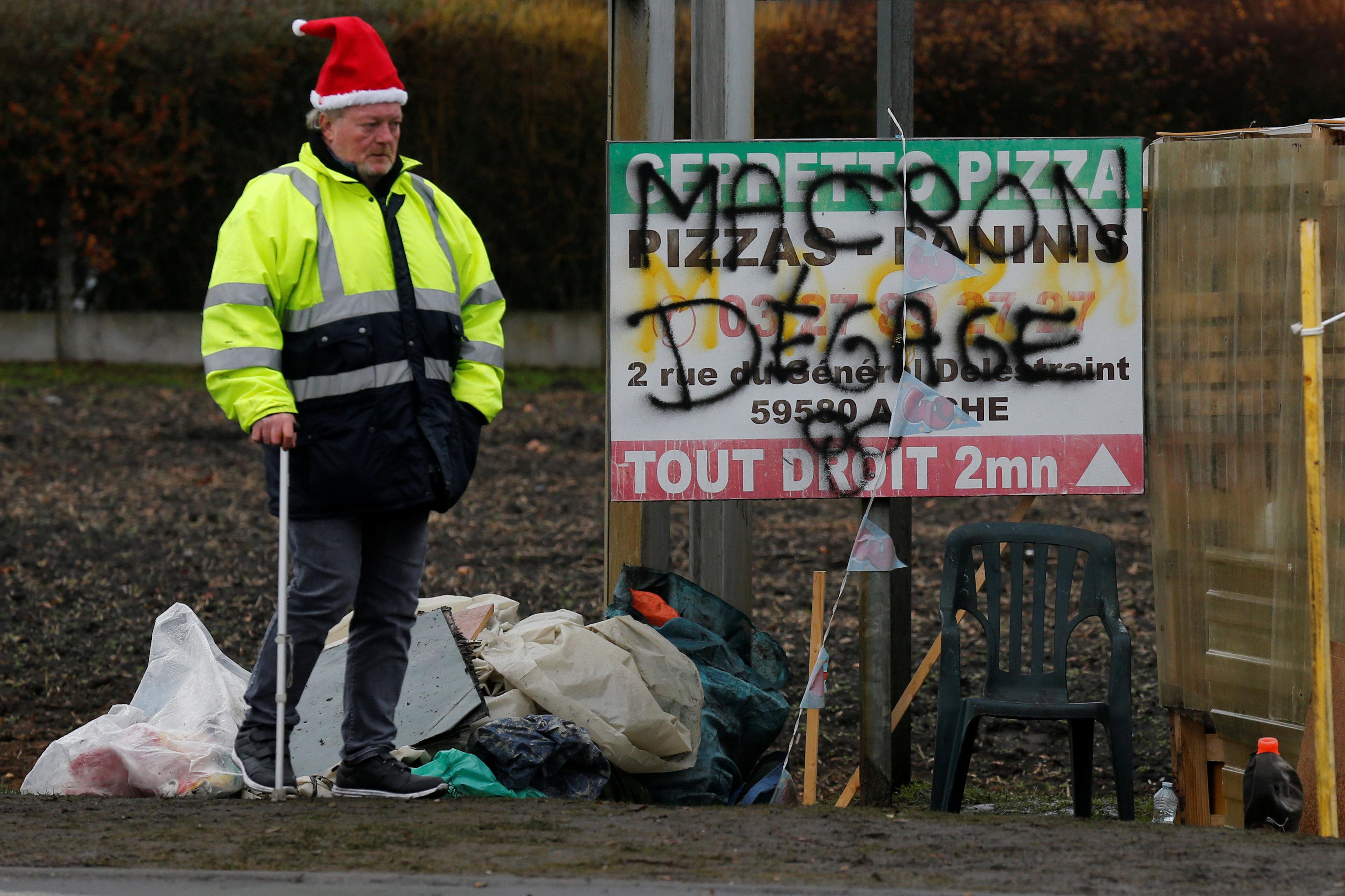 متظاهر يرتدى قبعة  بابا نويل وخلفة لافتة مناهضة لماكرون