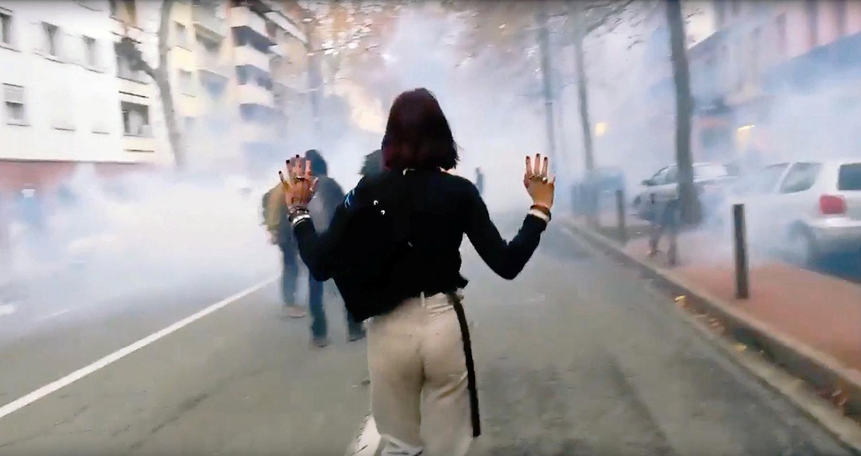 متظاهرة فى الشارع وسط انتشار للدخان