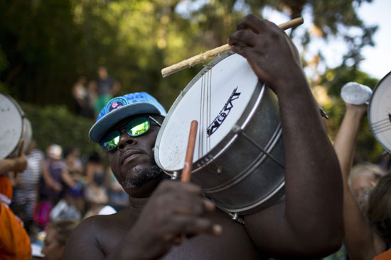 رجل يحمل طبلة خلال المشاركة فى الكرنفال