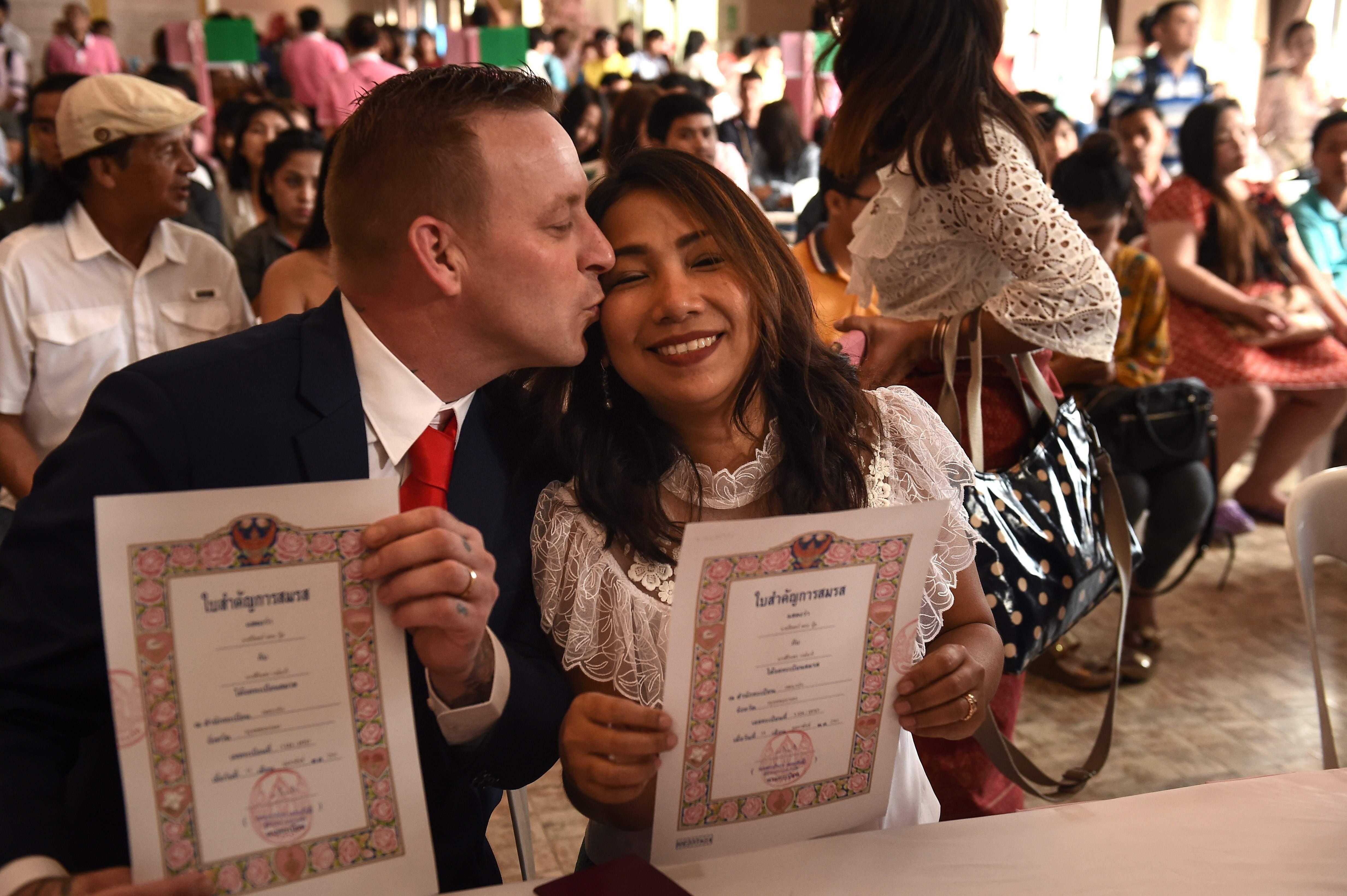 امرأة تايلاندية ورجل بريطاني يحملان شهادات زواجهما فى عيد الحب