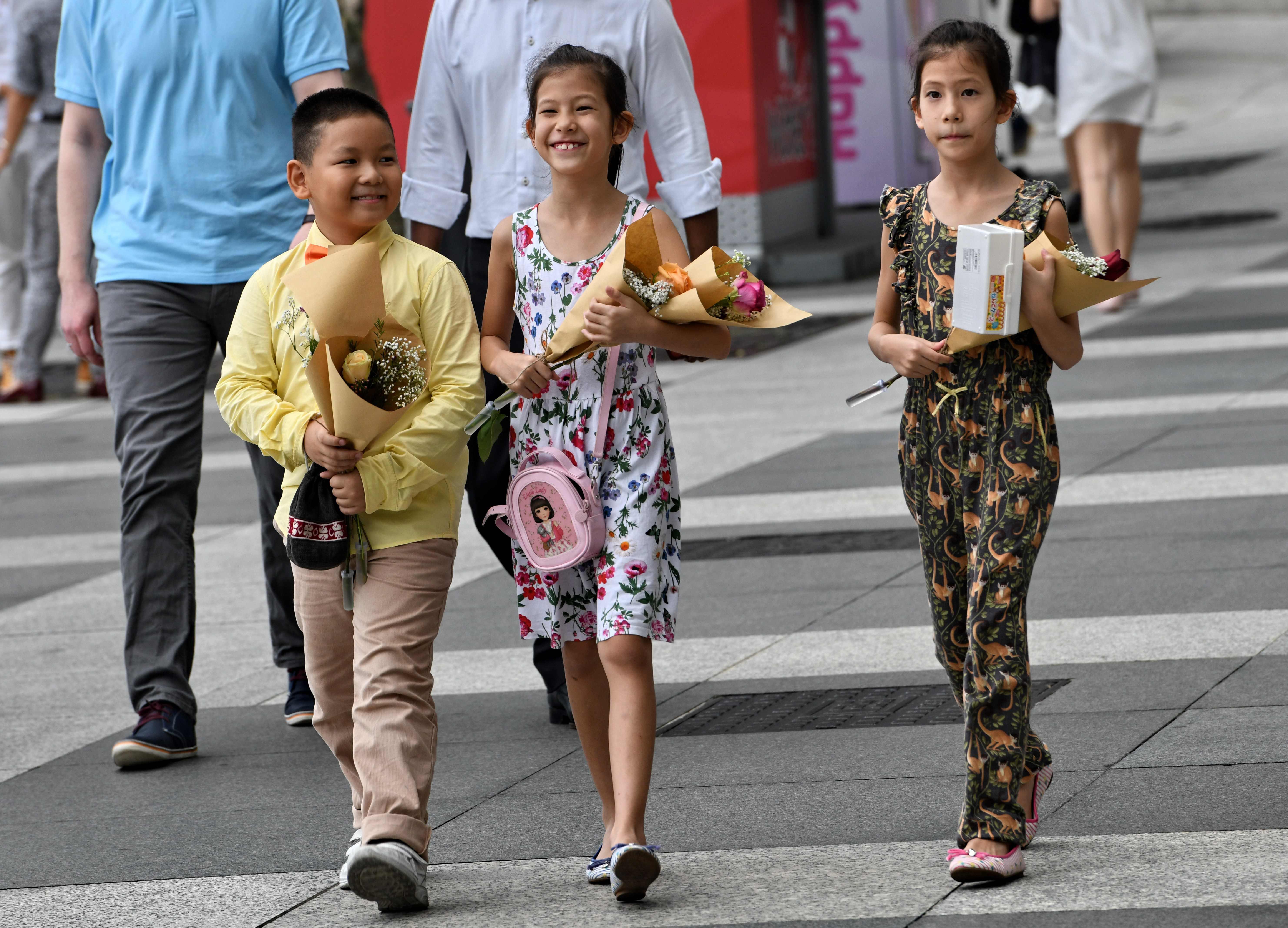 أطفال يحملون الورود احتفالا بعيد الحب