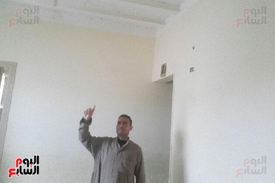 صاحب المنزل يشير الى السقف  وتشطيب الحجرة
