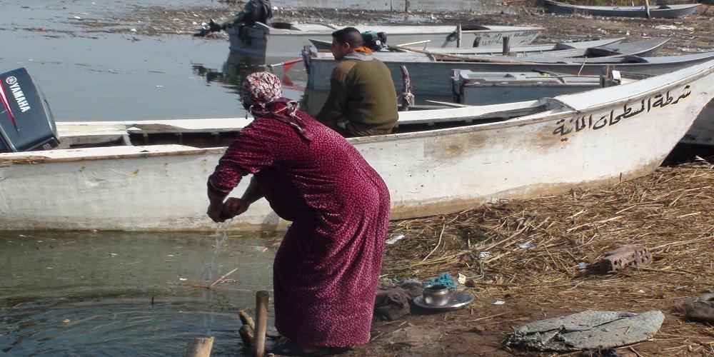 سيدة تغسل الملابس بمياه البحيرة