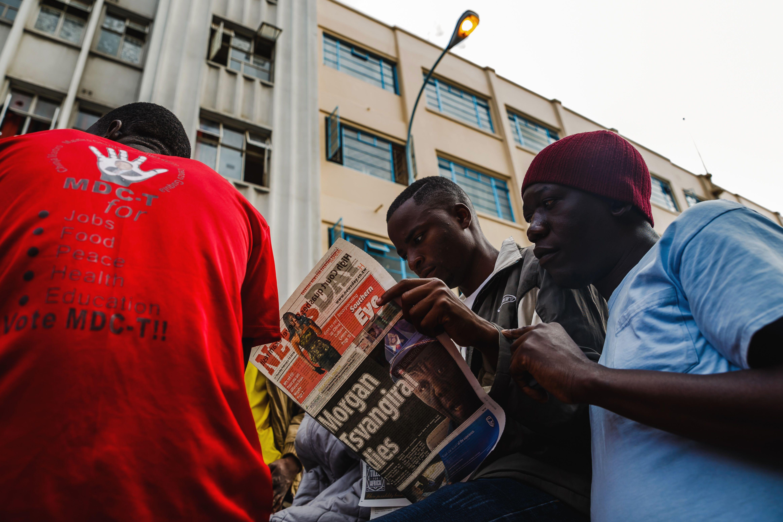 شباب يقرأون الخبر فى إحدى الصحف
