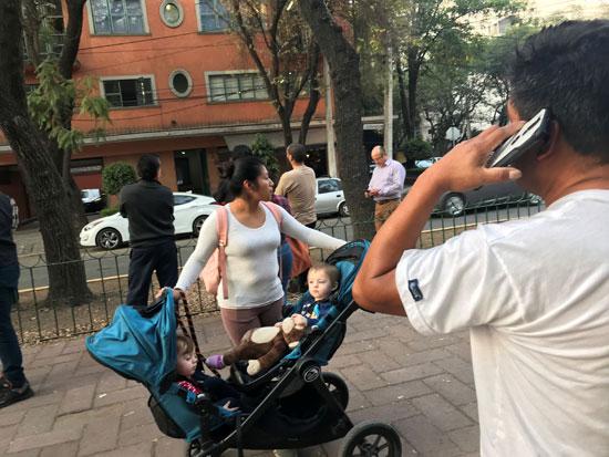 سيدة تقف وسط الشارع باطفالها