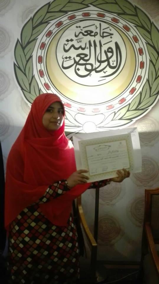 الطالبة مع شعار جامعة الدول العربية بعد فوزها بالمسابقة