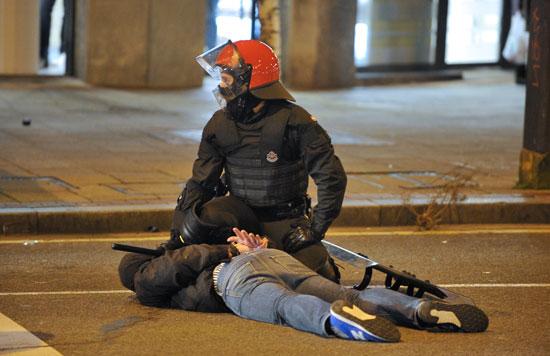 أحد عناصر الشرطة يعتقل مشجع