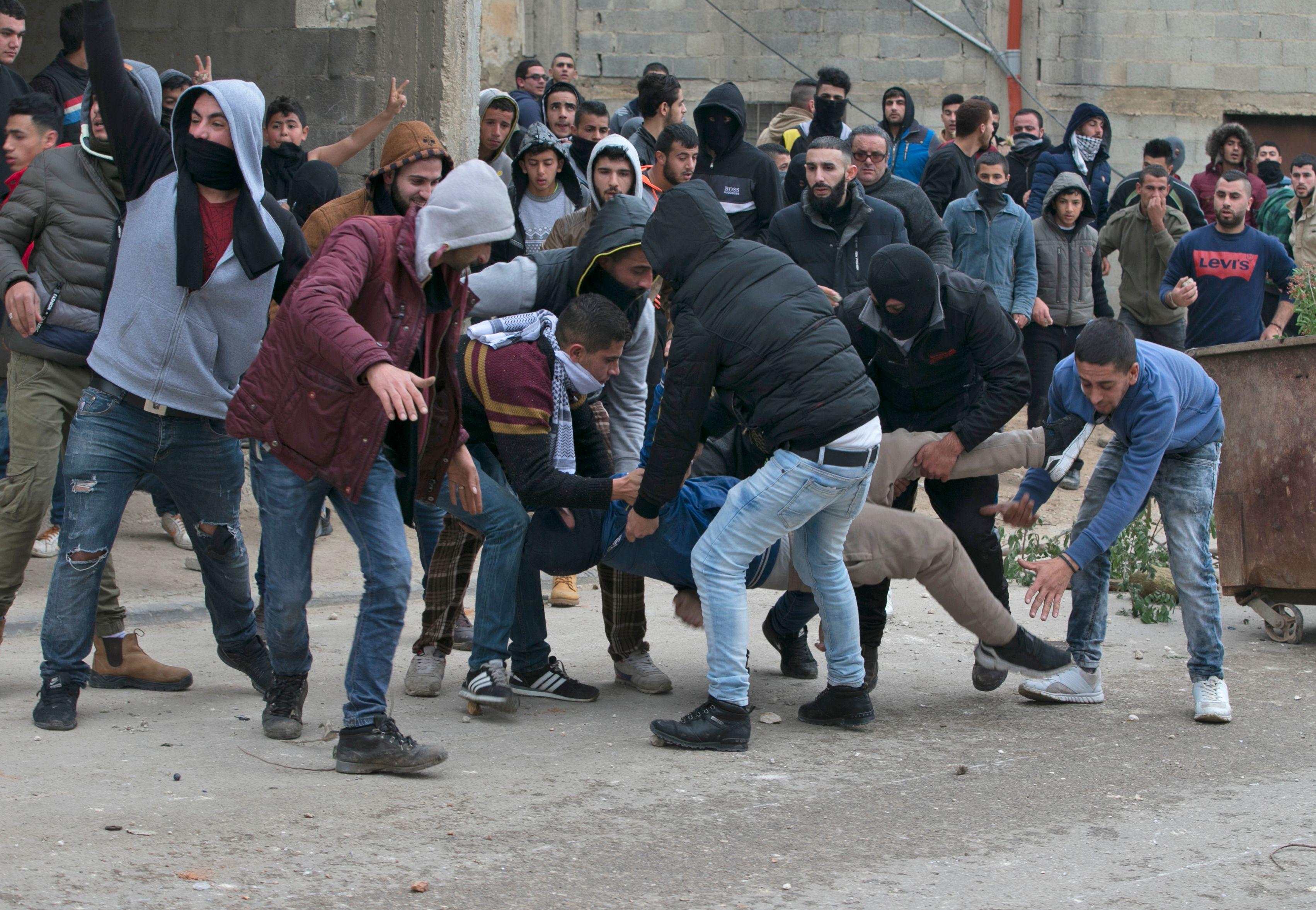 متظاهرون فلسطينيون ينقلون زميلهم المصاب خلال مواجهة الاحتلال