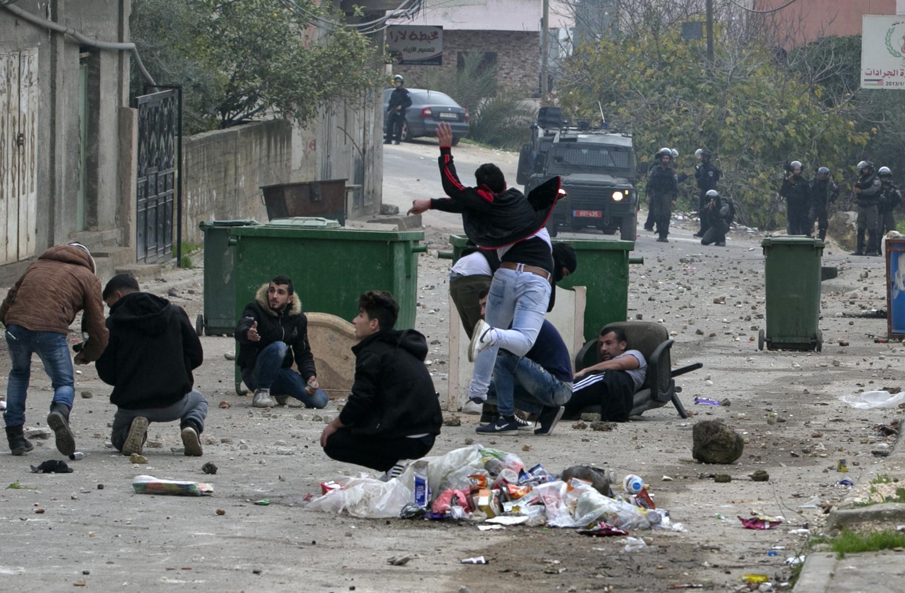 متظاهرون فلسطينيون يحتمون من رصاص قوات الاحتلال