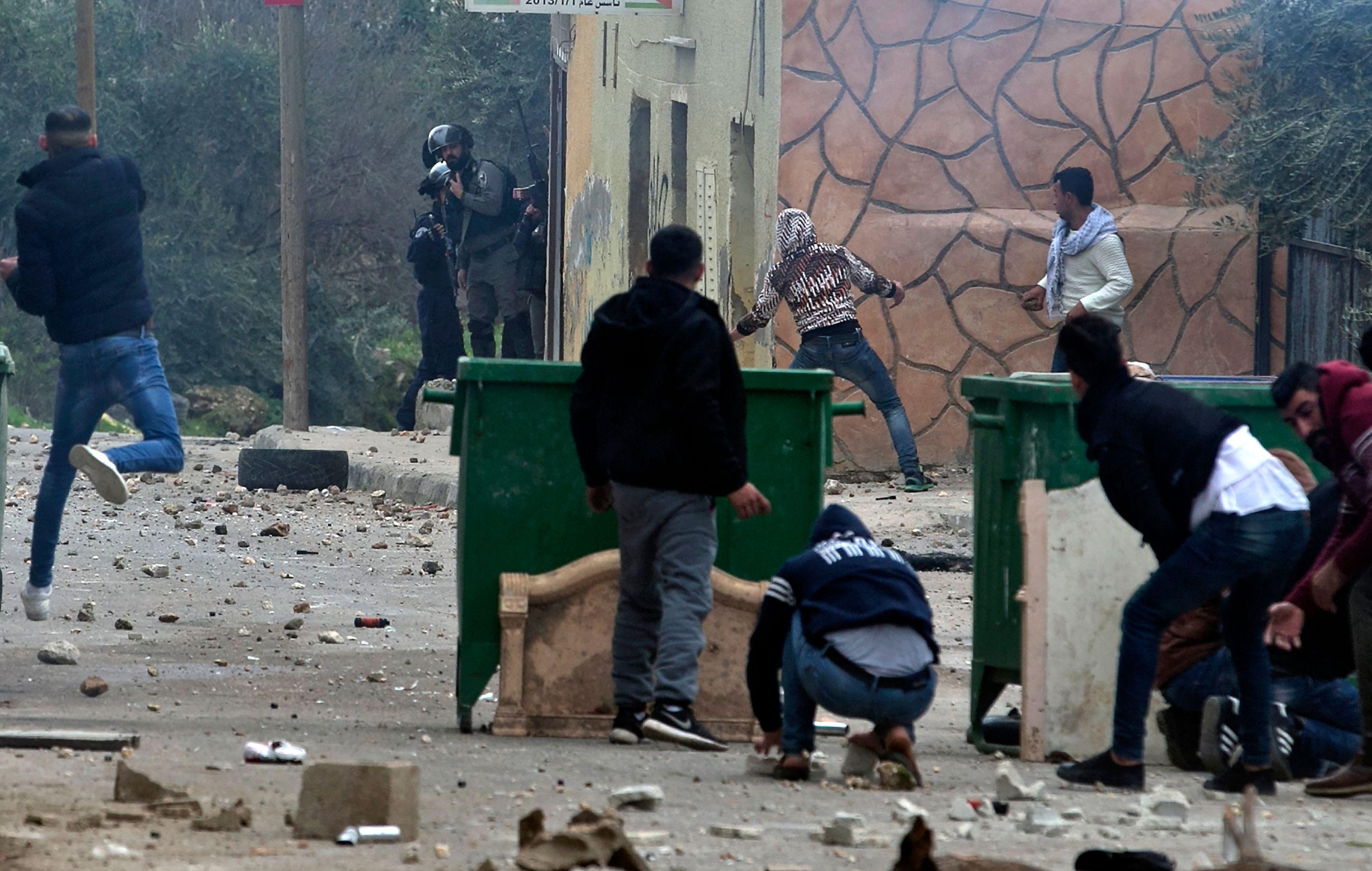 شباب فلسطينى يلقى الحجارة صوب قوات الاحتلال