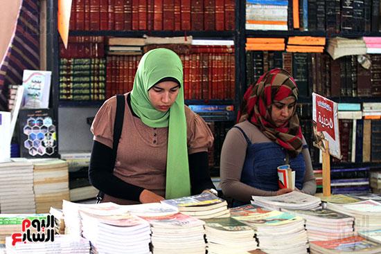 فتاتان يبحثان عن الكتب