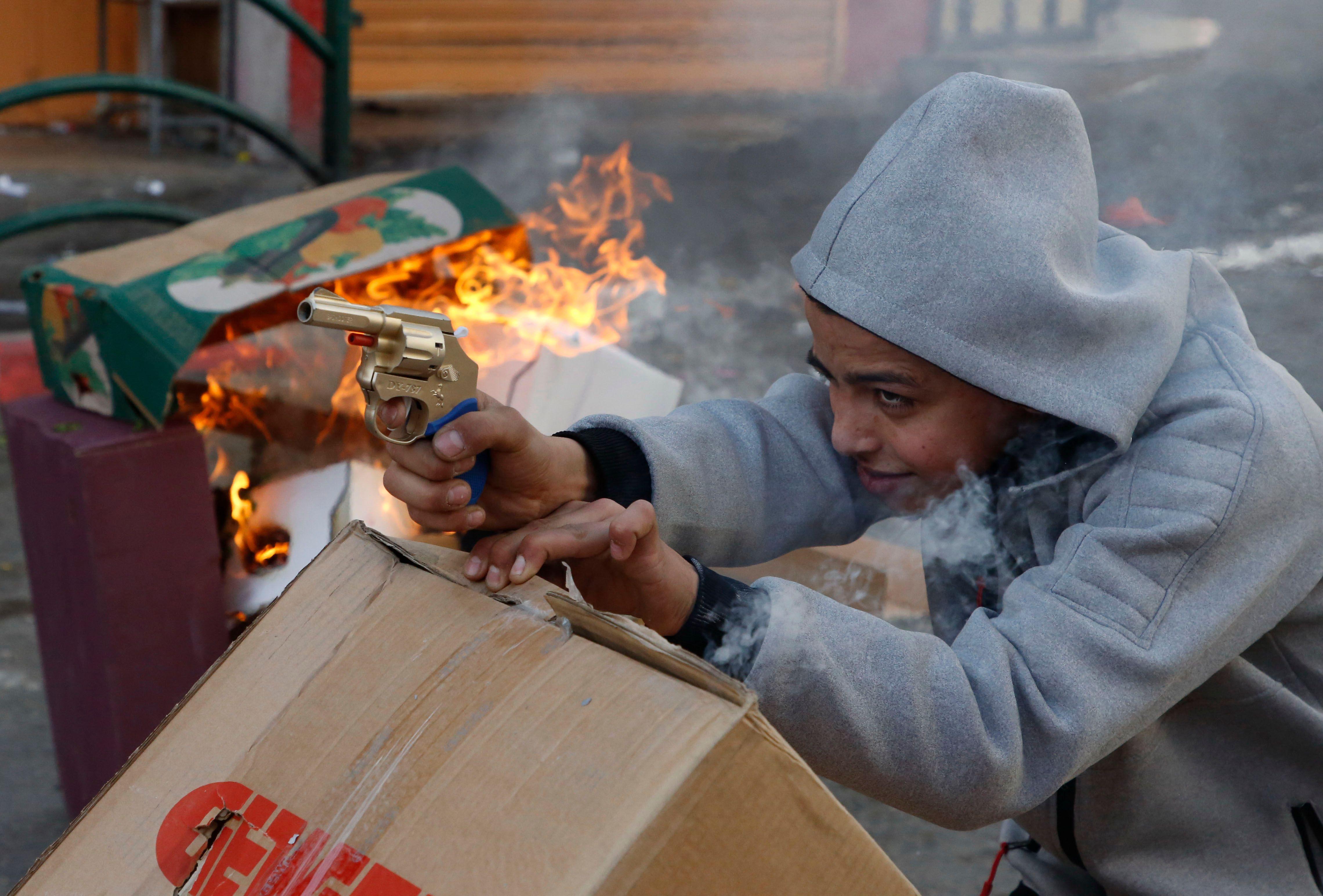 الطفل الفلسطينى ممسكا بمسدسه البلاستيك