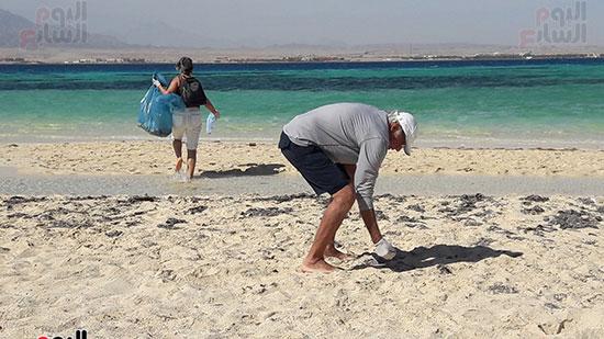 احد المشاركين خلال حمع المخلفات من الجزيرة