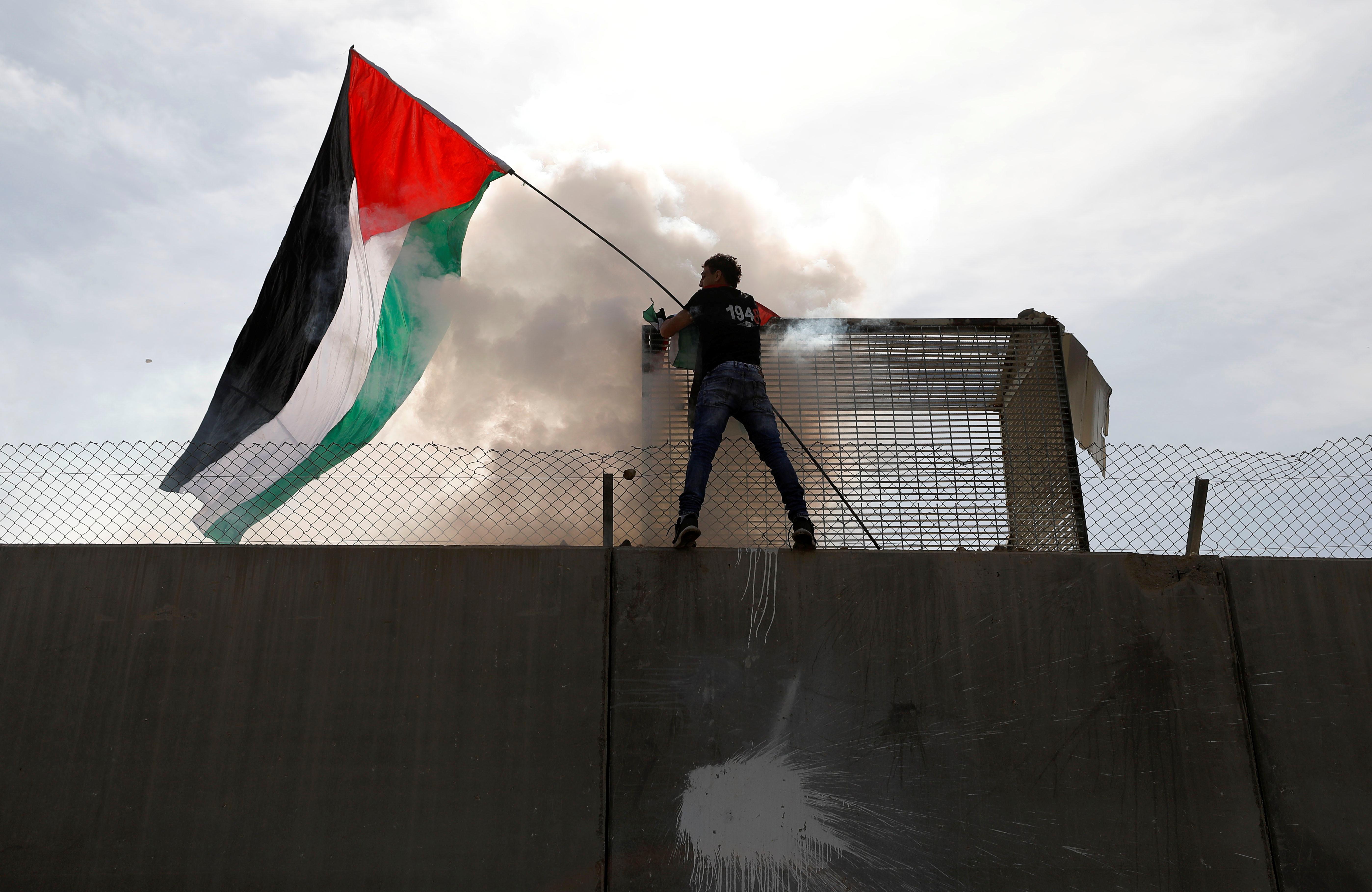 أحد الفلسطينيين يعتلى الجدار العازل