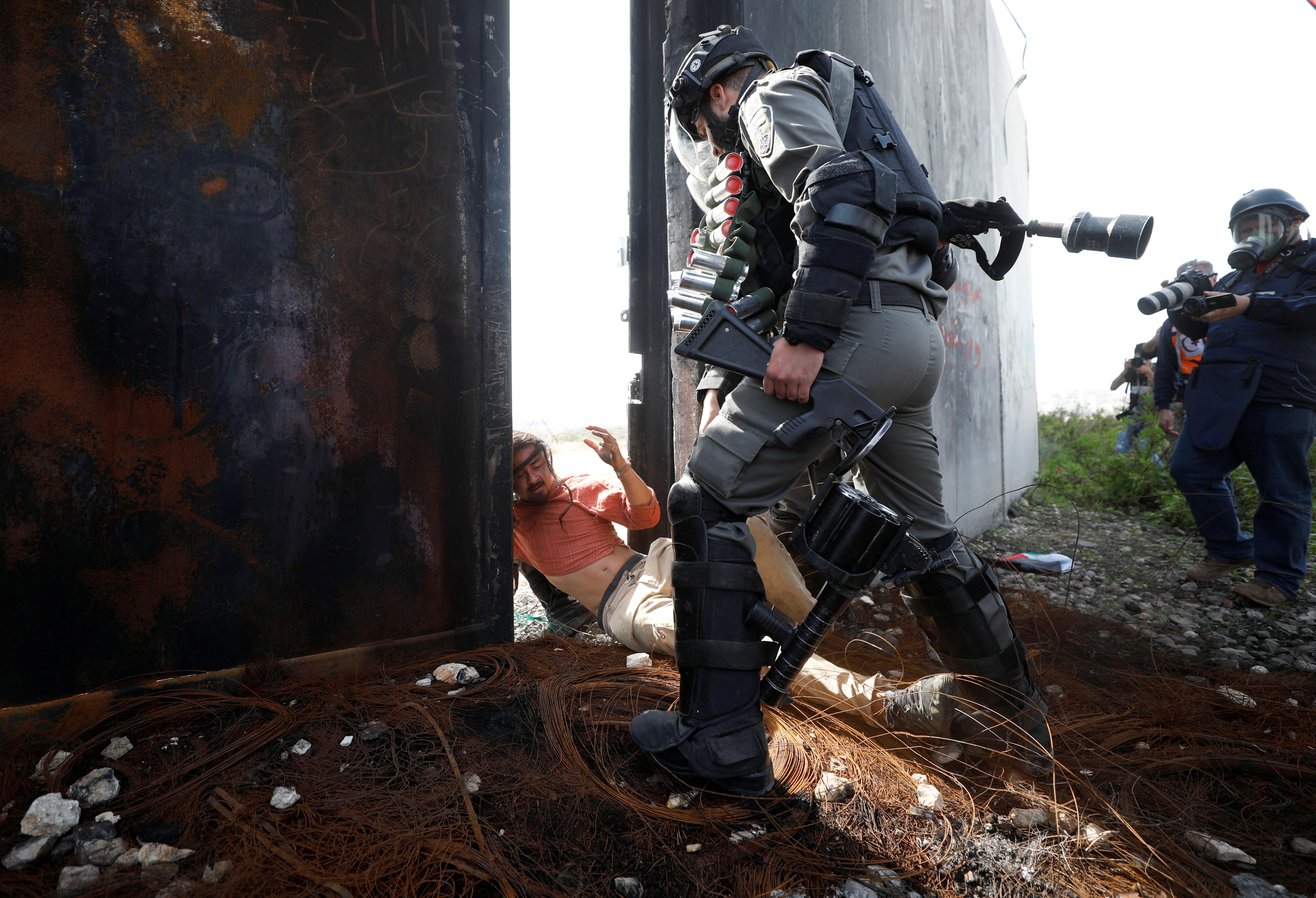 جندى إسرائيلى ينكل بأحد المتظاهرين