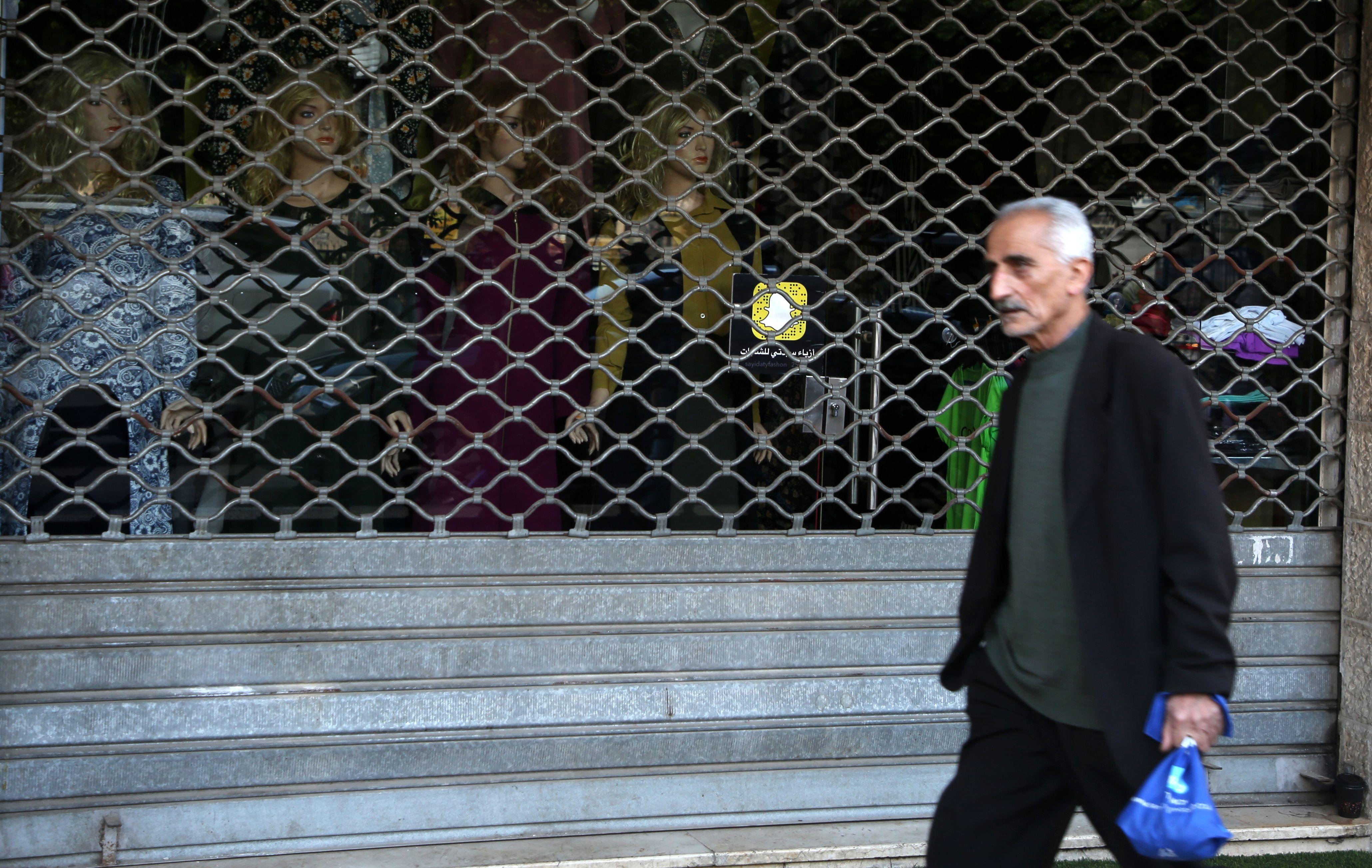 فلسطينى يمر أمام المحلات المغلقة بسبب الإضراب الشامل