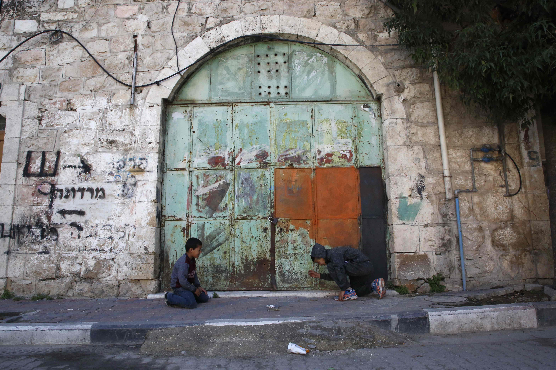 أطفال فلسطينيون يعلبون أمام المحلات المغلقة بسبب الإضراب