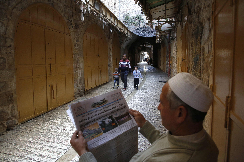 رجل فلسطينى يقرأ الجريدة فى الشارع أثناء الإضراب الشامل