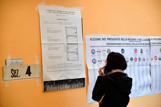 ناخبة تطلع على اللوحة الإرشادية للانتخابات فى إيطاليا