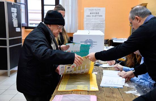 ناخب يطلع على أسماء المرشحين للانتخابات فى إيطاليا