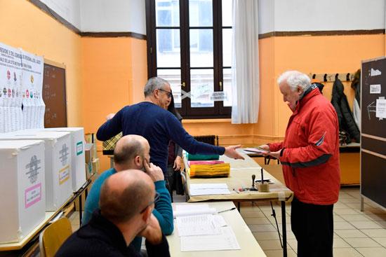 مراقب يطلع على أوراق ناخب بالانتخابات التشريعية الإيطالية