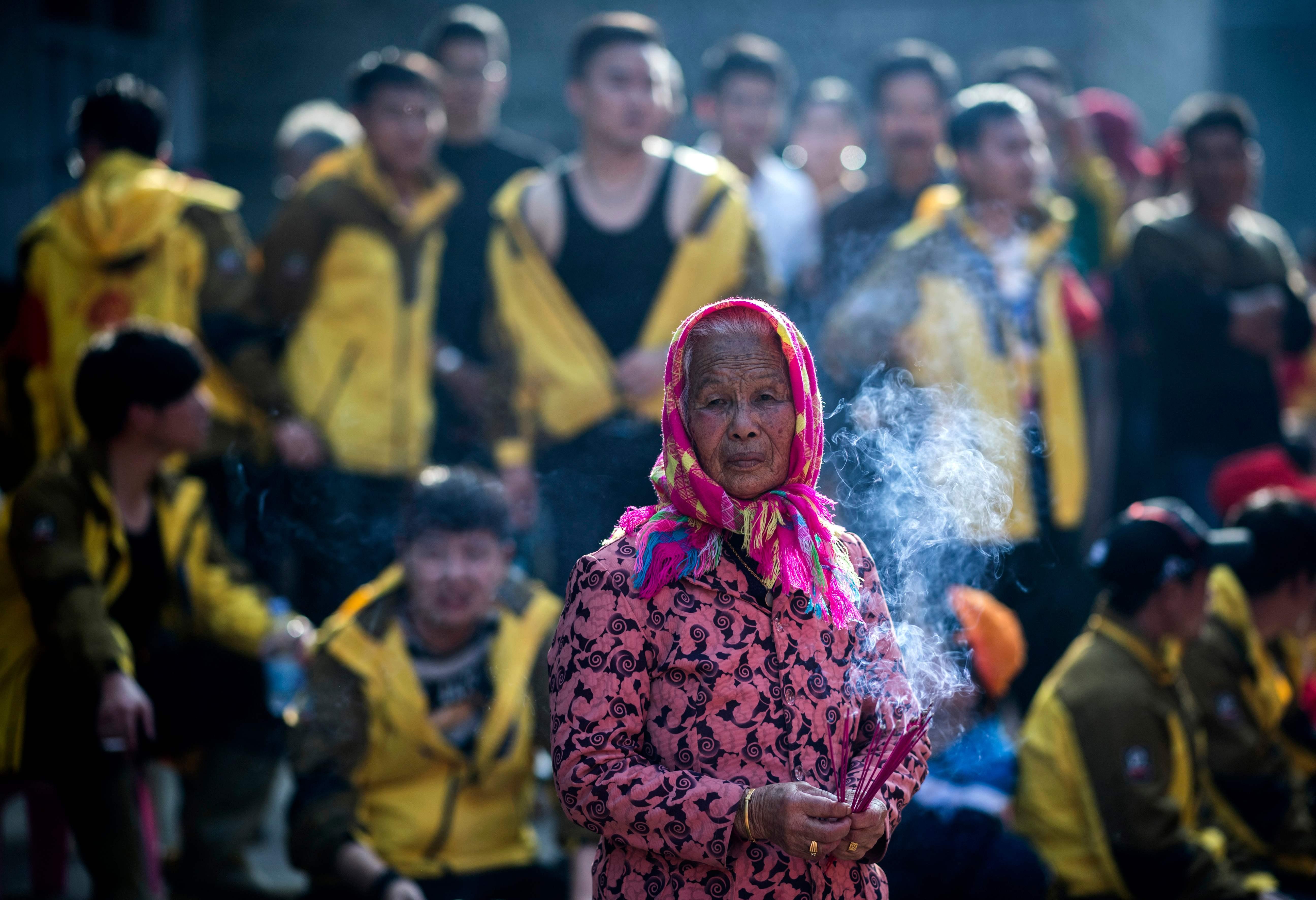 امرأة مسنة تشعل البخور