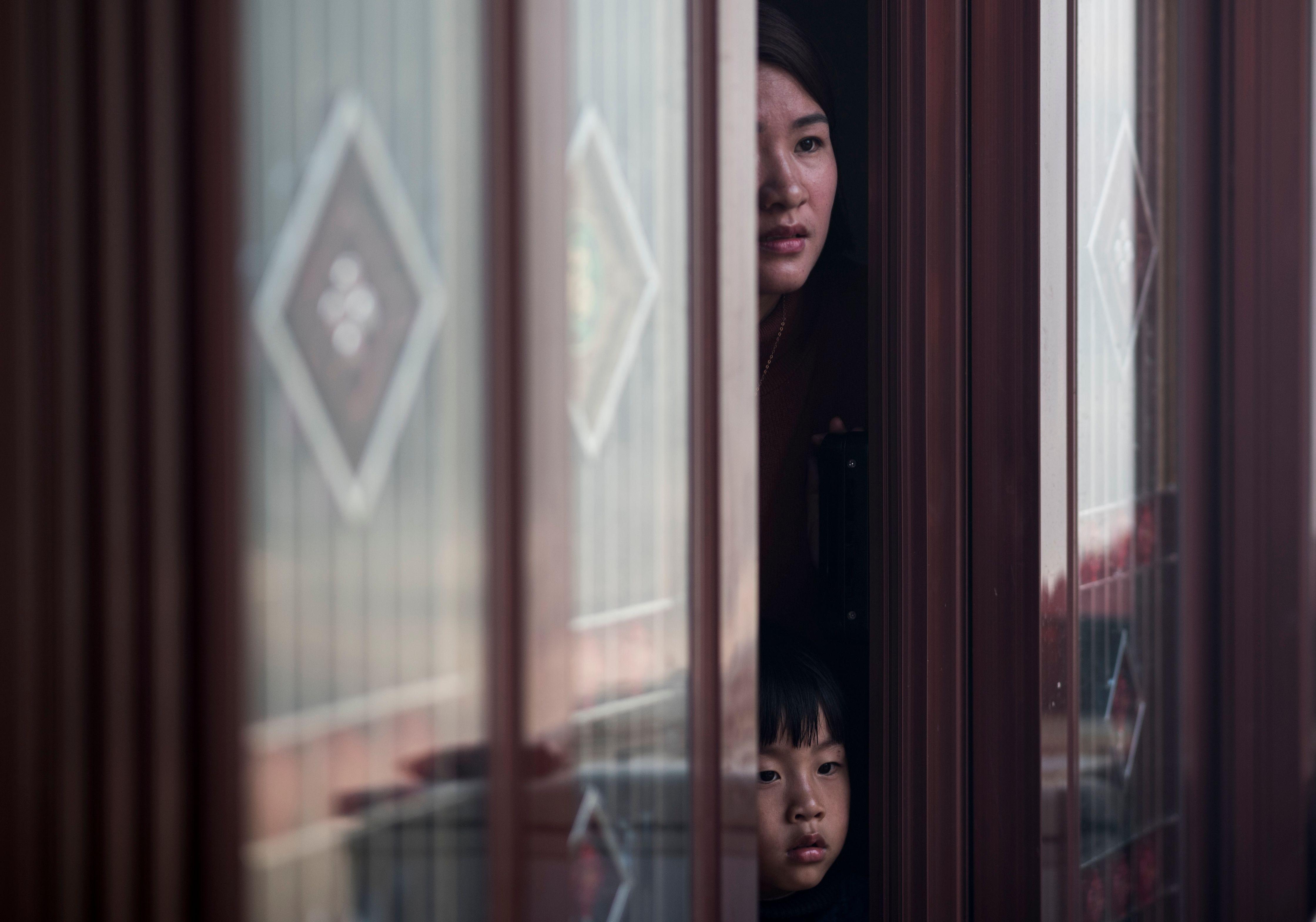 سيدة وطفلها ينظرون إلي الموكب