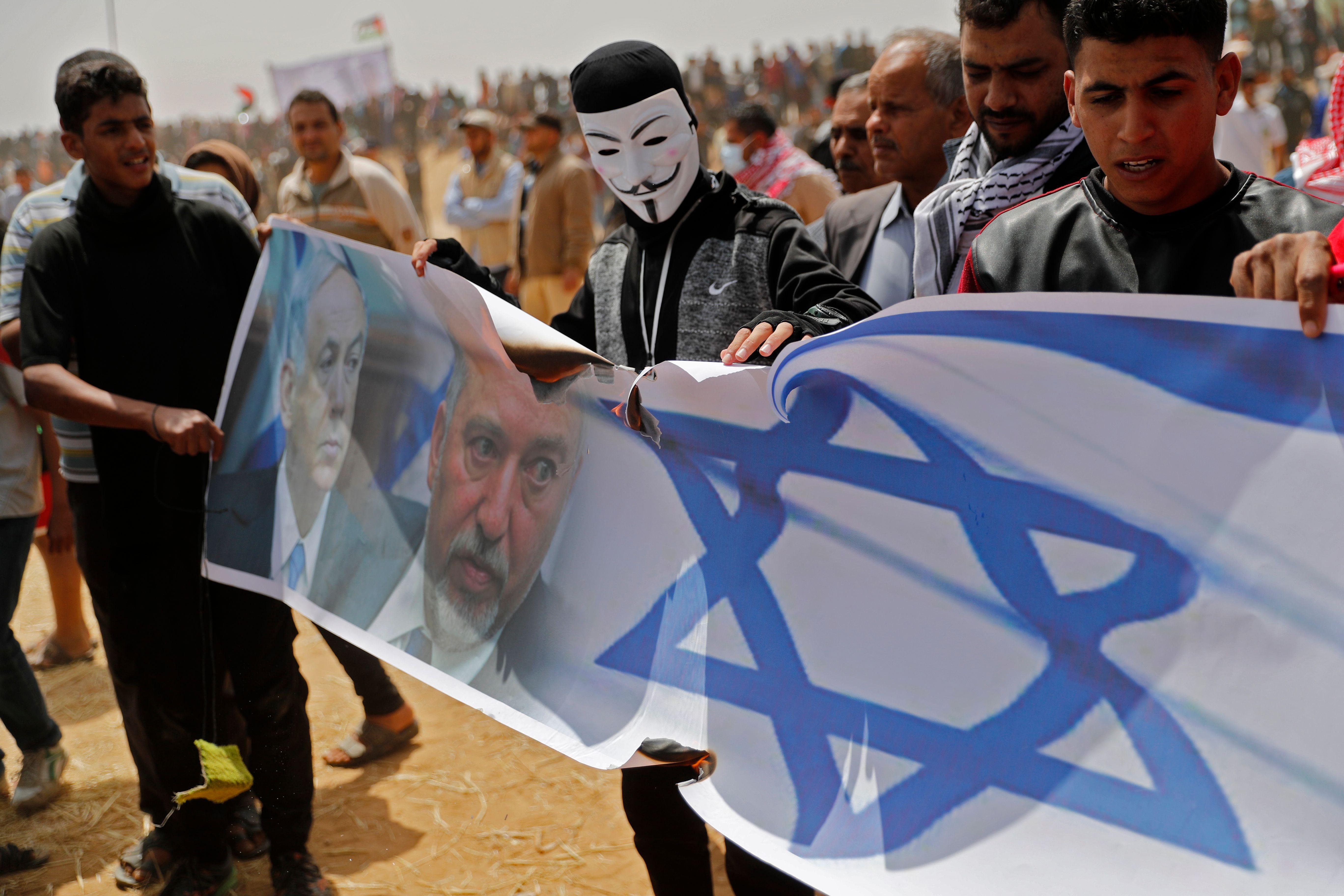 فلسطينيون يحملون أعلام إسرائيل تنديدا بالاحتلال