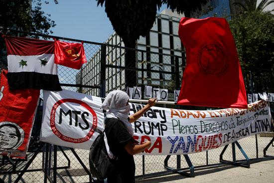 المتظاهرون فى مكسيكو سيتى يضعون العلم السورى على سور السفارة الأمريكية