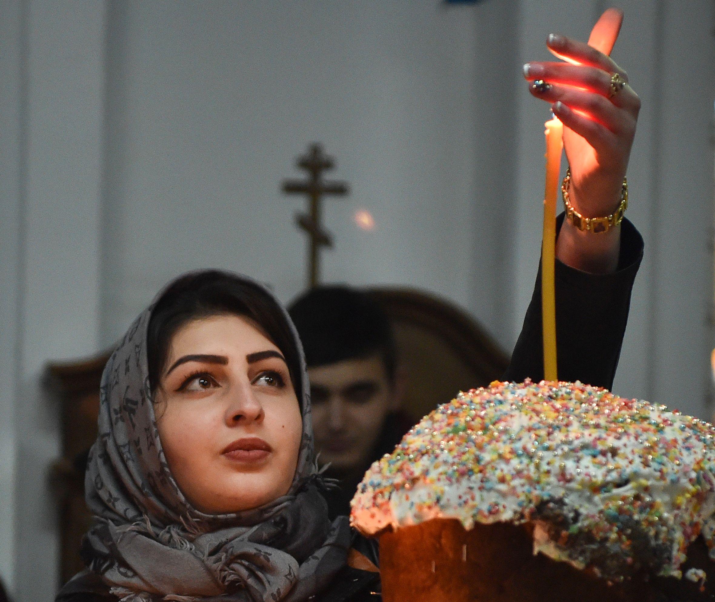 سيدة تضيئ شمعة خلال  خلال مراسم عيد الفصح فى كازاخستان
