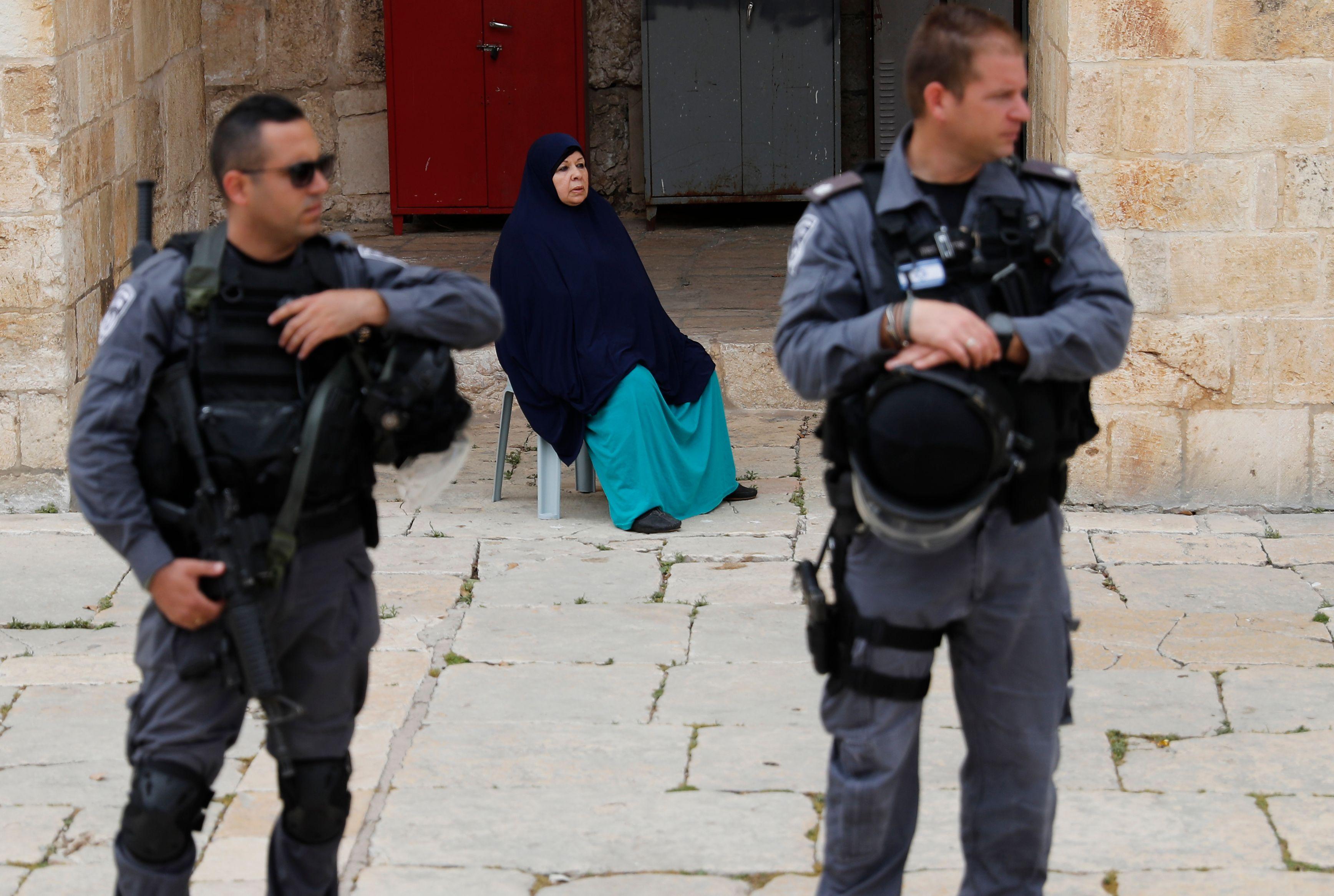 سيدة تجلس خلف جنود الاحتلال