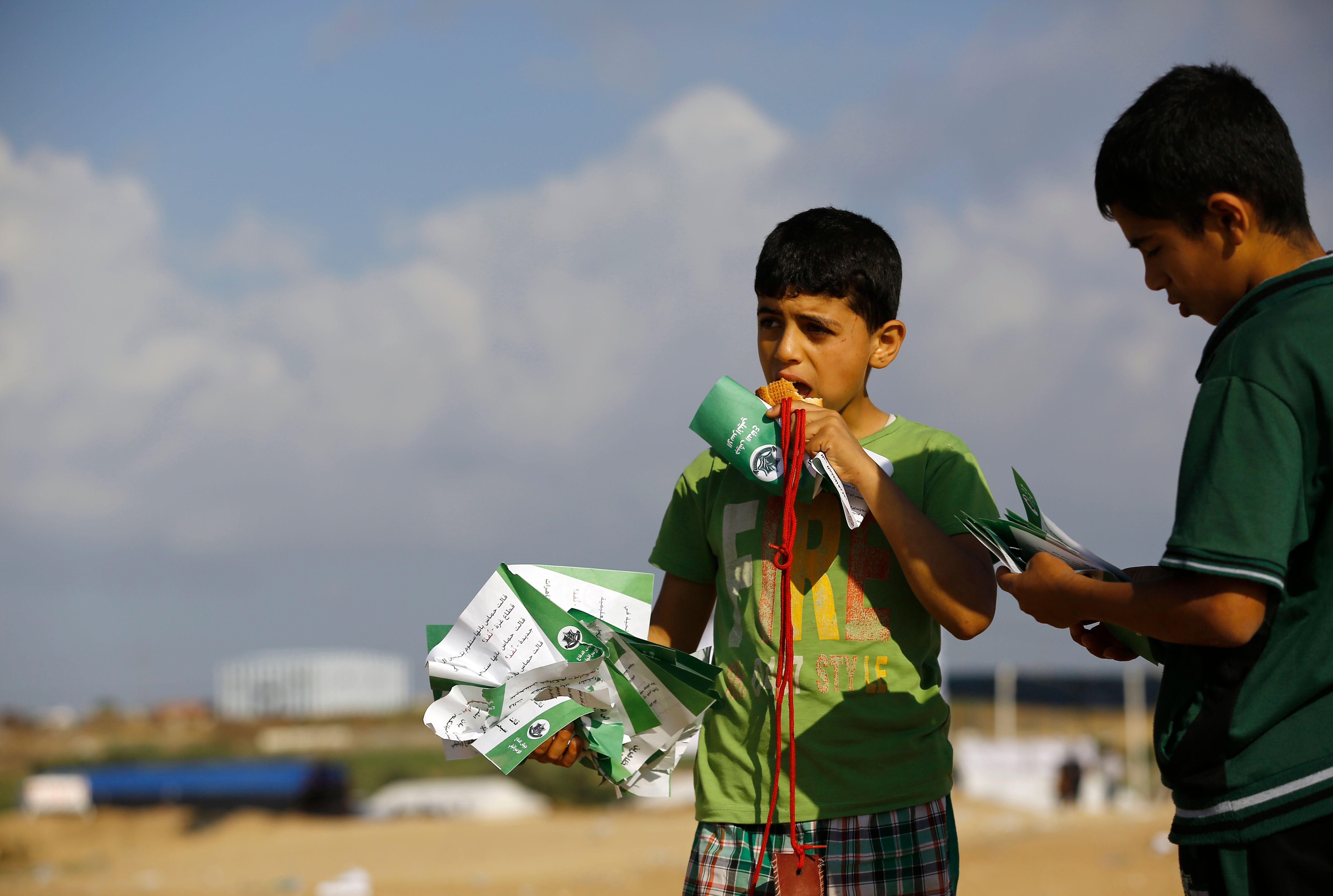 طفل فلسطينى يحمل منشورات التحذير الإسرائيلية