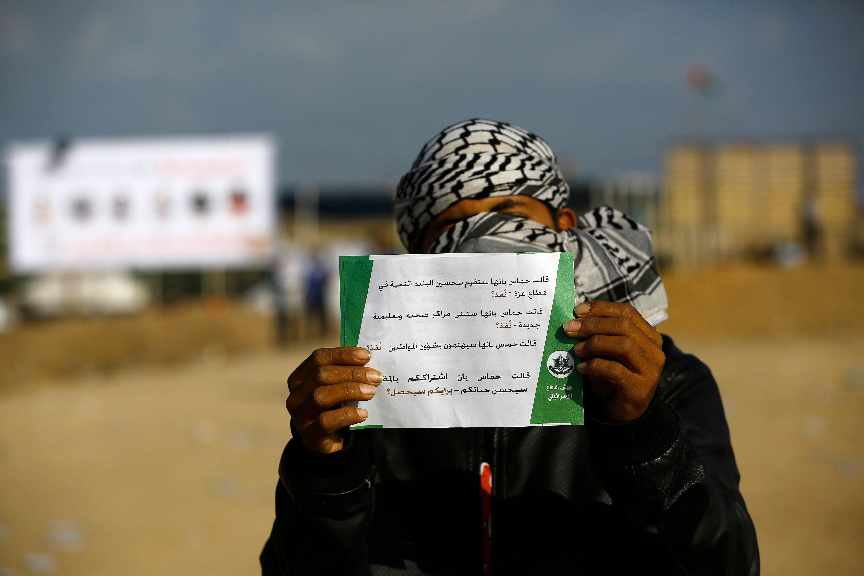 شاب فلسطينى يحمل منشور تحذيرى من الاحتلال الإسرائيلى