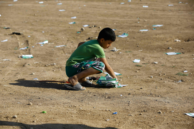 طفل فلسطينى يجمع منشورات الاحتلال التحذيرية