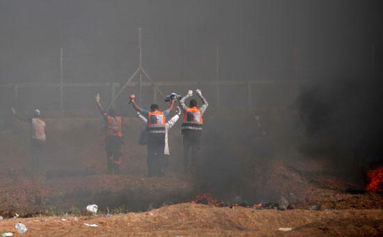 مسعفون فلسطينيون ينقلون المصابين من منطقة الاشتباكات بغزة