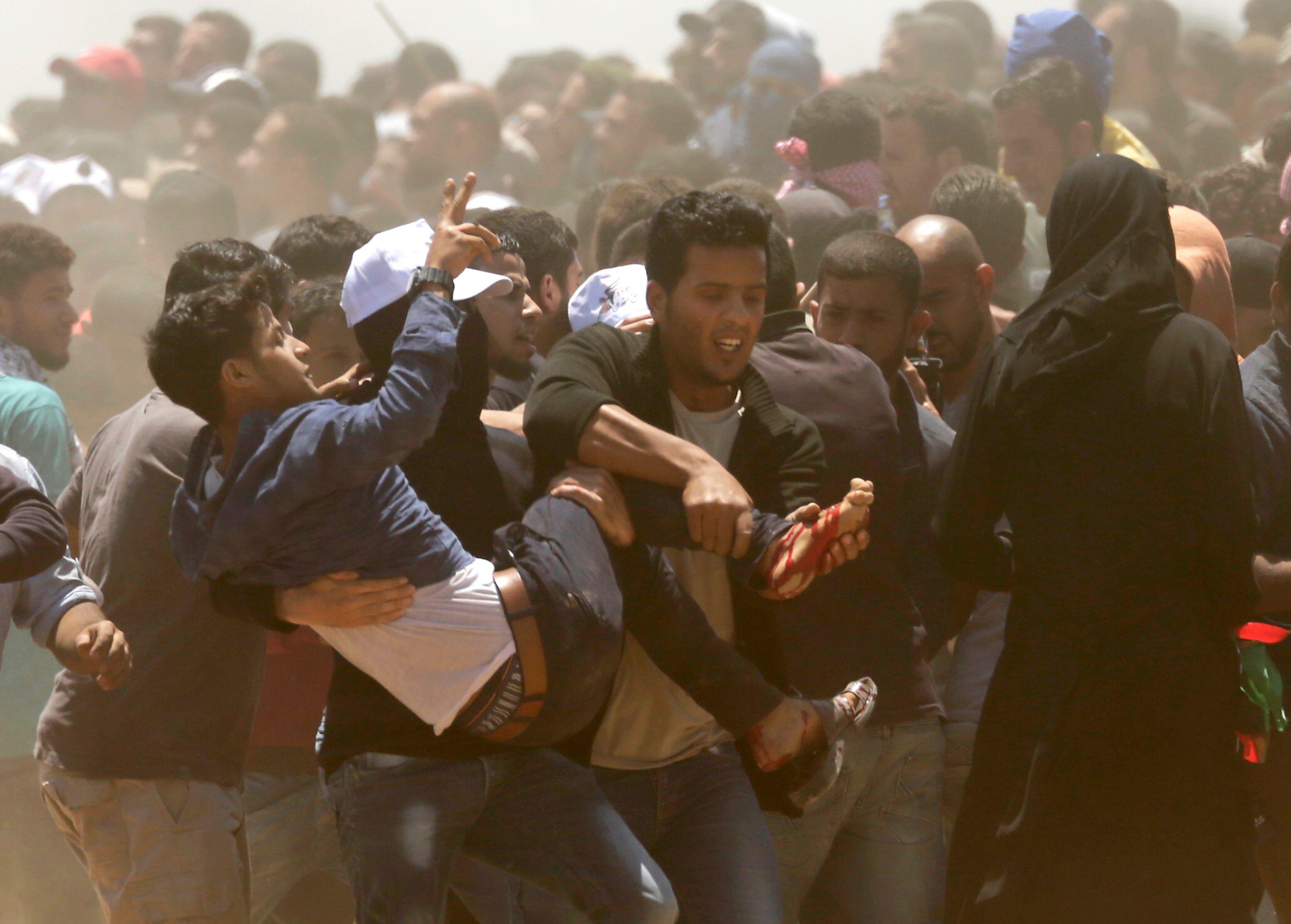 شباب فلسطينيين يحملون صديقهم المصاب فى مواجهة الاحتلال