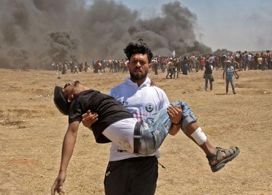 شاب فلسطينى يحمل صديقه المصاب برصاص الاحتلال