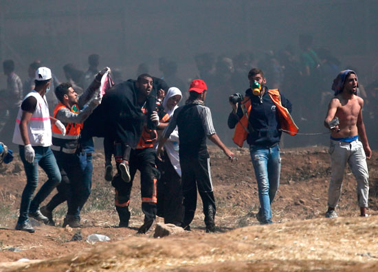 نقل مصاب فلسطينى من منطقة الاشتباكات على حدود غزة