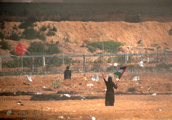 سيدة فلسطينية ترفع علم بلادها فى مواجهة جنود الاحتلال
