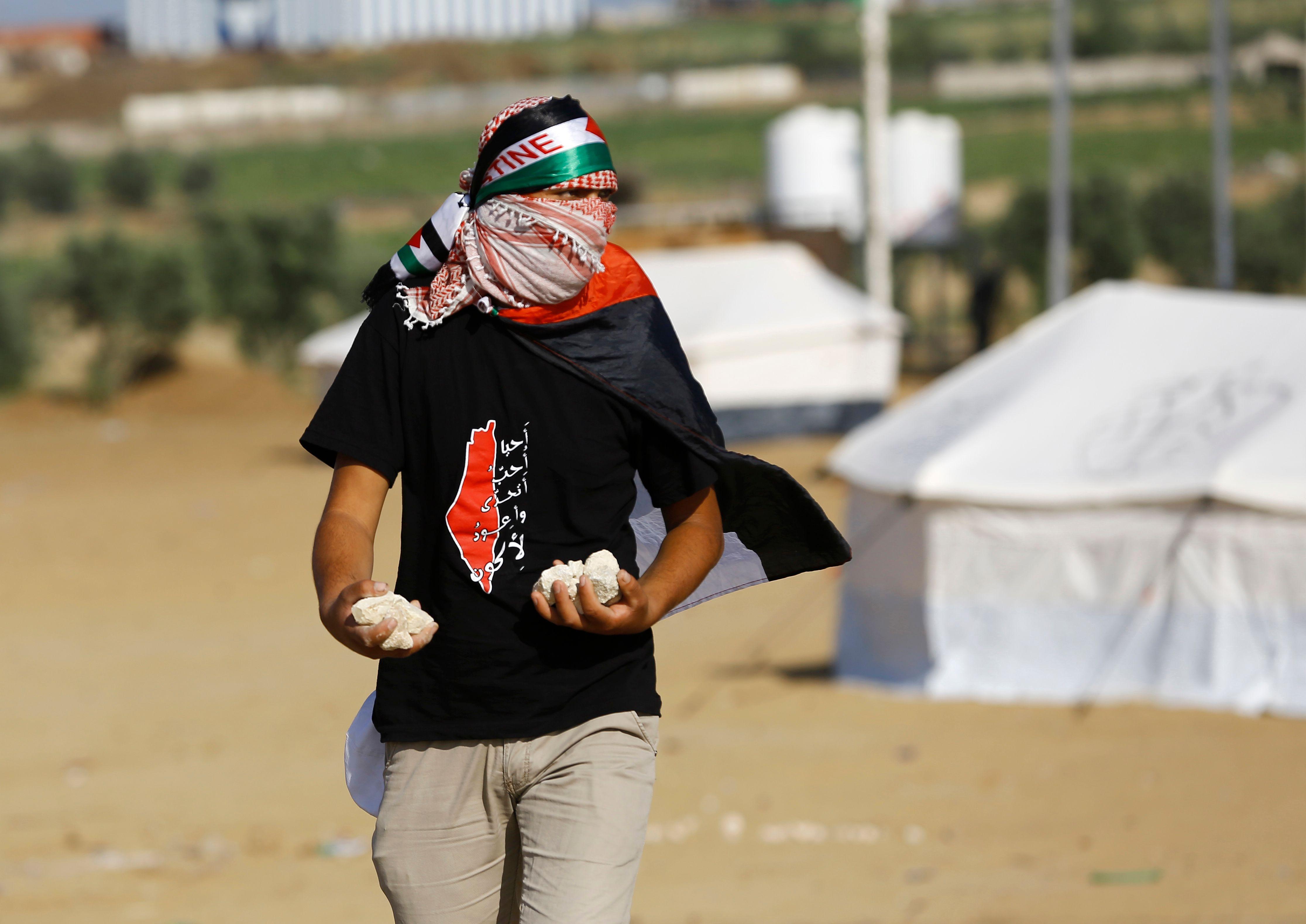 شاب فلسطينى يعد الحجارة لمواجهة رصاص الاحتلال بغزة