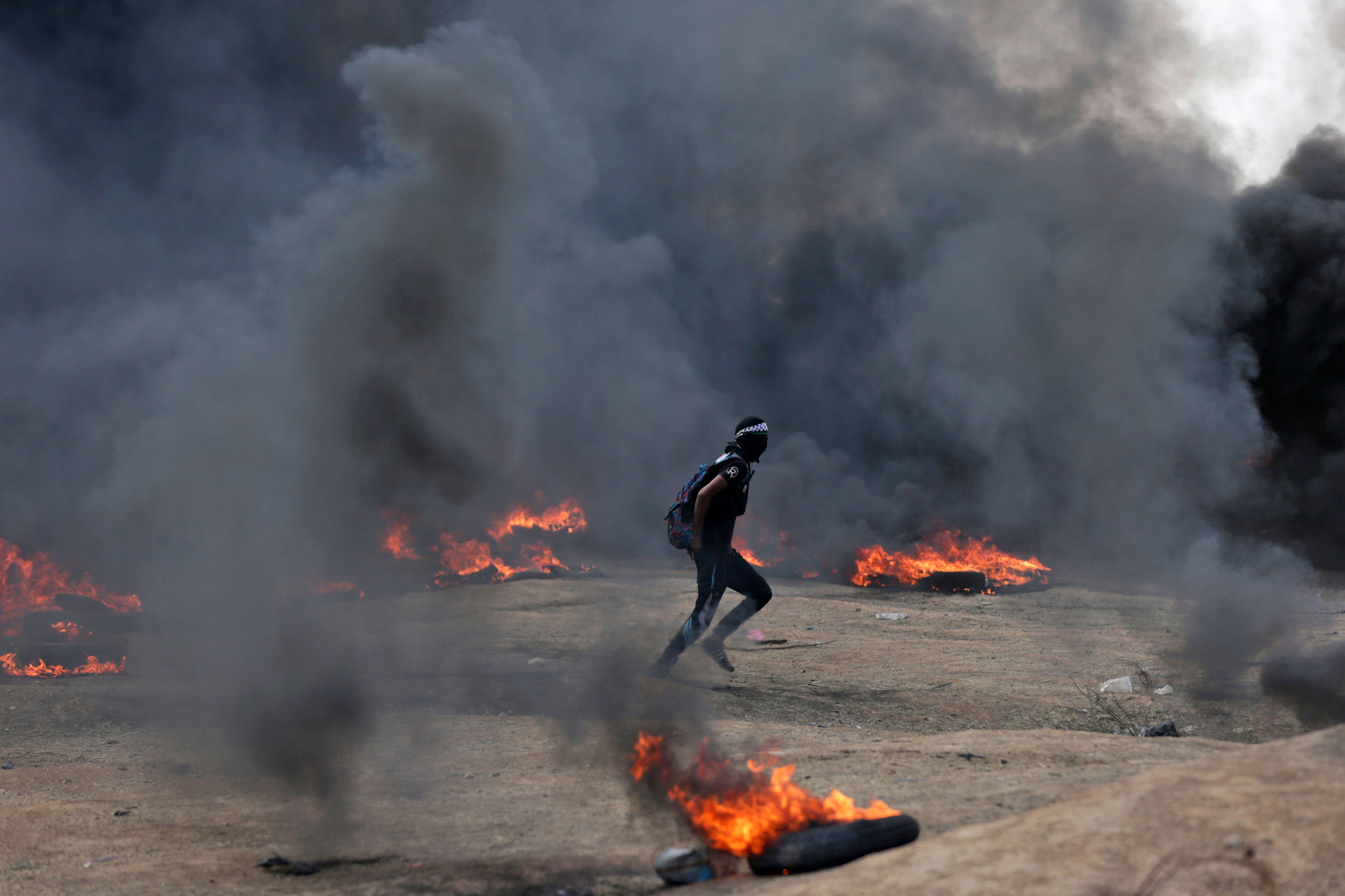 شاب فلسطينى يهرول وسط النيران على حدود غزة